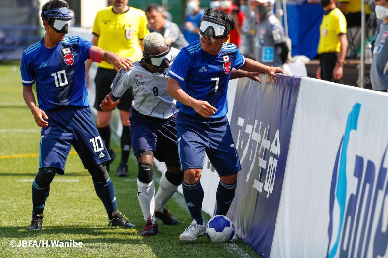 フェンス際の攻防/田中章仁選手と川村怜選手がボールをキープ